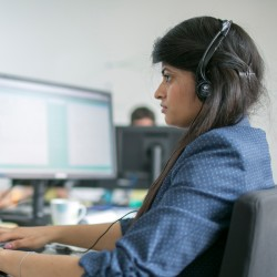 Person wearing headset looking at screen while typing