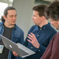 Three people standing discussing while looking at notebook screen