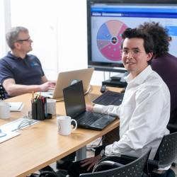 Three people in office one facing the camera